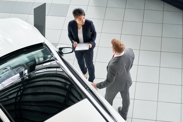 Saleswoman giving an advice to her client on the car at salon
